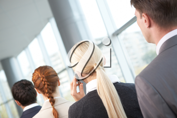 Rear view of business woman calling among her colleagues