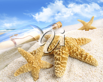 Royalty Free Photo of a Bottle and Starfish on the Sand