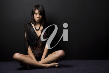A fashion shot of a beautiful asian girl sitting on the floor