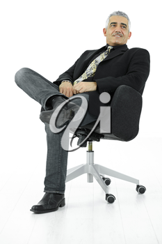 Portrait of mature businessman sitting in office chair in confident pose. Isolated on white.