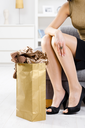 Closeup photo of female hands packing out of shopping bag, legs in stockings and shoes.
