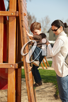 Mother helping little boy to climb wooden climbing wall on playground, sunlit outdoor.