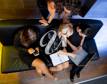Team of attractive businesswoman having a meeting sitting on couch, using laptop computer and handheld. Overhead shot.