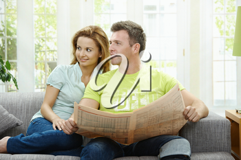 Love couple reading newspaper together on couch at home, smiling.