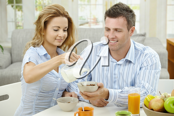 Couple having healty breakfast at home, eating cereals, fruits and drinking orange juice.