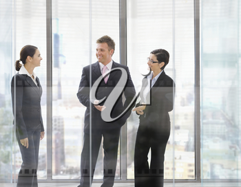 Three happy businesspeople standing in front of office windows, talking and smiling.