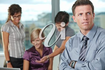 Confident businessman at office with business team in background.