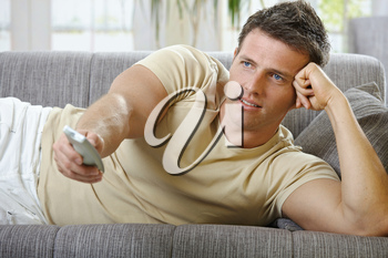 Handsome man in causal wear smiling lying on sofa with remote control handheld, watching television