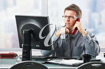 Focused businessman listening to explanation of computer report on landline phone looking at screen sitting in office.