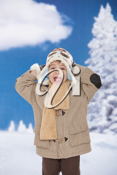 Portrait of happy kid wearing warm clothes in snow on a cold winter day, smiling.
