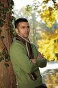 Outdoors portrait of happy young man standing in autumn park at tree, looking away, thinking.
