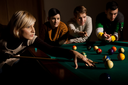 Woman concentrating on snooker game, leaning on table, aiming at ball, holding cue, friends watching in background.