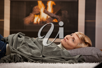 Woman resting at home lying on floor in front of a fire place,
