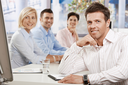 Happy businessman sitting at table in meeting room at office, looking at camera smiling