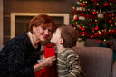 Little boy leaning to smiling grandmother with eyes closed, getting surprise christmas present.