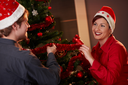 Happy young couple wearing santa claus hat, celebrating christmas, smiling.