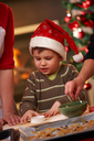 Small boy in santa claus hat helping at christmas baking watching mother and grandmother making cake.