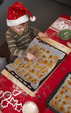 Small boy sitting at table pointing at christmas cake in baking pan.
