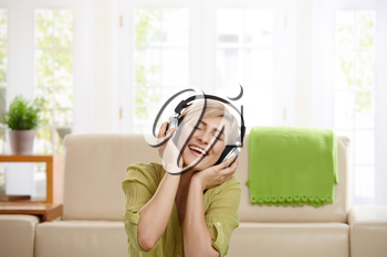 Happy woman listening to music on headphones at home, laughing.