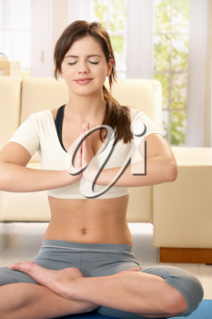 Girl doing yoga meditation sitting on living room floor with closed eyes, smiling.