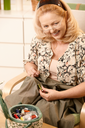 Smiling senior woman sitting in armchair, looking for matching colour of thread to shirt in sewing kit.