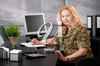 Senior woman sitting at office desk working, looking at camera smiling.