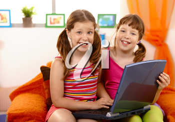 Young girls sitting on couch using laptop computer, laughing.