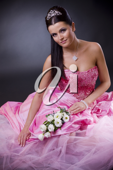 Smiling young bride sitting in a pink wedding dress, holding bouqet of white flowers.