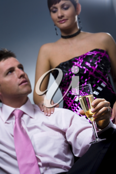 Couple drinking champagne on a party. Selectvie focus placed on the glass.