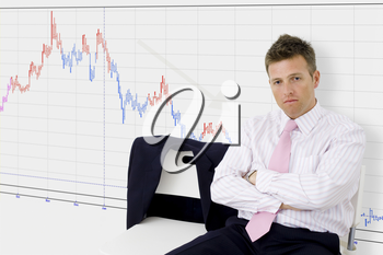 Disappointed businessman sitting in front of chart showing economic recession.