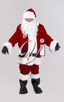 Full size portrait of Santa outspreading arms, looking down, isolated on gray background.