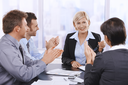 Business team celebrating businesswoman at meeting, clapping hands.