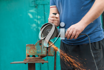 The worker cuts off a strip of metal, hand-held by an electric saw.