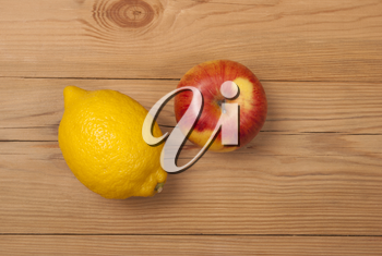 Lemon and apple on a wooden background. View from above .