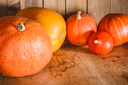 Pumpkins on grunge wooden backdrop, background table. Autumn, halloween, pumpkin