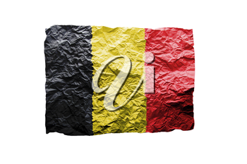 Close up of a curled paper on white background, print of the flag of Belgium