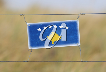 Border fence - Old plastic sign with a flag - Kosovo