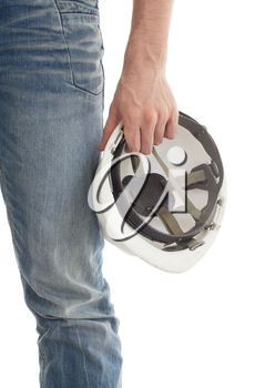 Male engineer in jeans holding white hardhat, isolated
