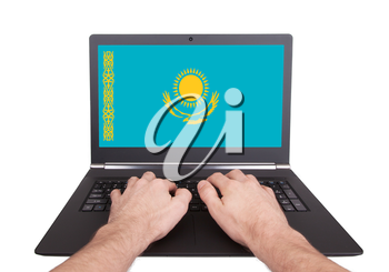 Hands working on laptop showing on the screen the flag of Kazakhstan