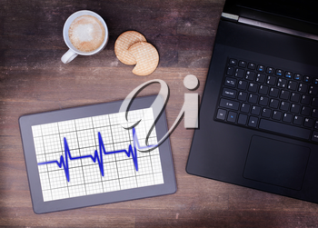 Electrocardiogram on a tablet - Concept of healthcare, heartbeat shown on monitor - blue