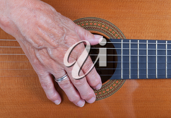 Close up on an old woman's hand playing guitar