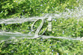 image with jet of falling water on the green background