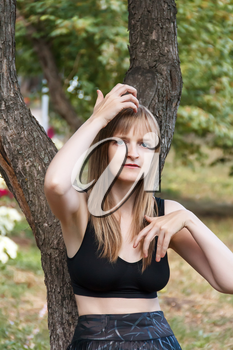Blond woman correcting hairstyle near tree in summer