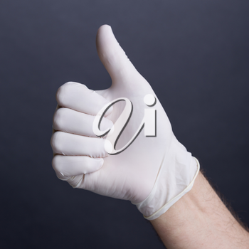 Male hand in latex glove (thumb up sign) on dark background