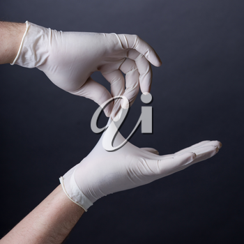 Male hands in golves. Doctor or nurse putting on latex gloves. Sanitary, healthcare, medical clothing. Dark background