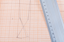 metal ruler at graph paper with dress pattern