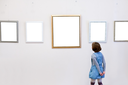girl sees a picture frames in art gallery