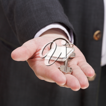 blank door keychain on businessman's palm close up