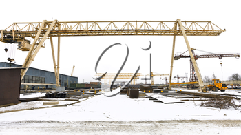 industrial landscape with bridge cranes and rolled metal products