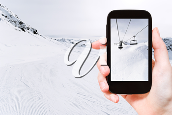 travel concept - tourist taking photo of skiing tracks and ski lift in Paradiski area, Alps, France on mobile gadget